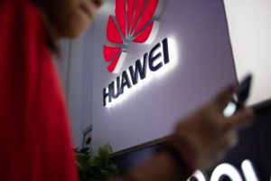 Man using Huawei mobile at the Huawei store and there's a logo of huawei company on the wall'